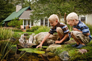 Two boys playing in the creek at the Cottages at Water's Edge,a fractional property at Crystal Mountain